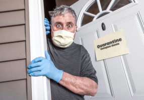 "Man wearing mask and gloves afraid of virus exposure with quarantine sign that says ""Quarantine Contagious Disease"""